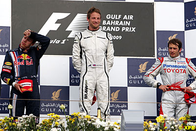 Vettel looks like he is ready to melt while Jenson does his Cheshire cat impression